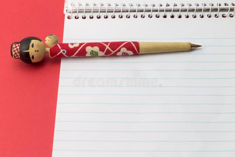 Penna för statyettbollpunkt på den tomma anteckningsboken med röd bakgrund - royaltyfria bilder