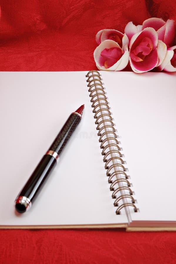 Penna, fiori e diario fotografie stock