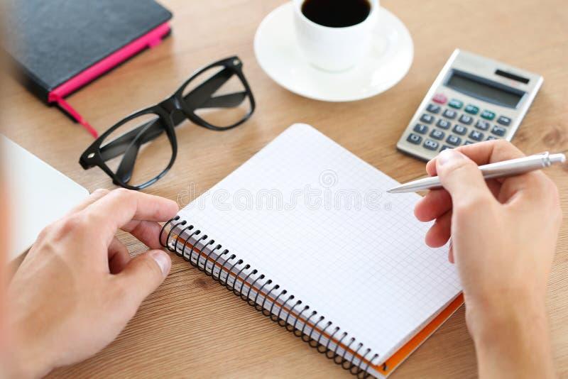 Penna maschio dell'argento della tenuta della mano pronta a fare nota in notebo aperto immagine stock libera da diritti