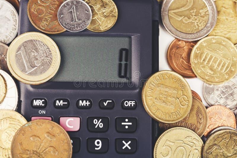 Penna, occhiali e grafici Il calcolatore circondato da varia valuta del mondo conia il primo piano fotografia stock libera da diritti