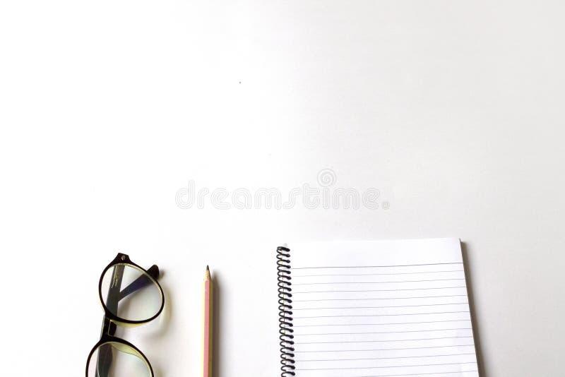 Penna och anteckningsbok p? en vit bakgrund arkivbild