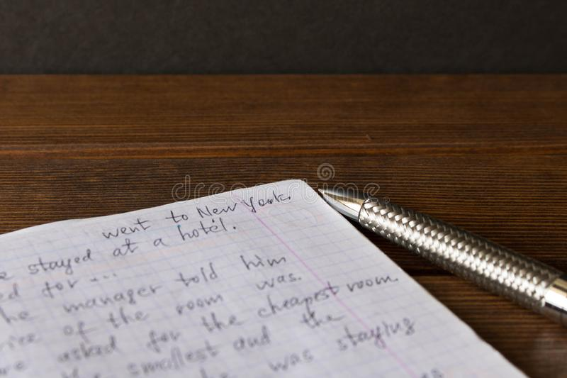 Penna och anteckningsbok som är på engelska på skolaskrivbordet Begreppet av e arkivbild