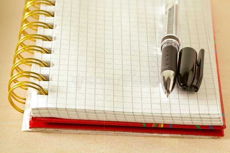 Penna och en anteckningsboksida i bur arkivbild