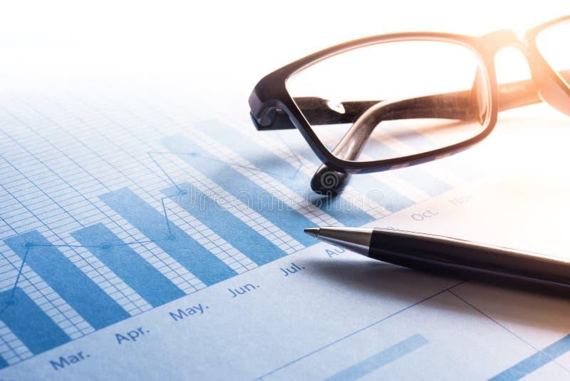 Penna och exponeringsglas på diagram för affärsgraf Affär och finansiellt royaltyfri bild