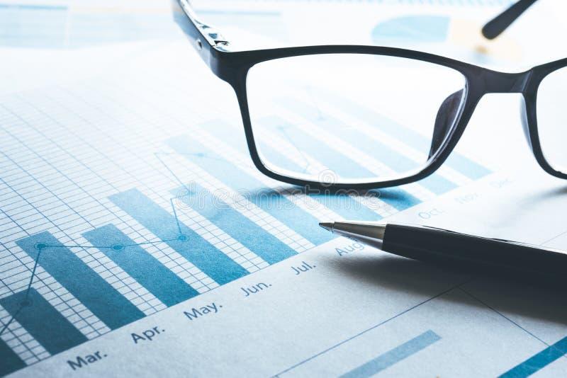 Penna och exponeringsglas på diagram för affärsgraf Affär och finansiellt arkivbilder