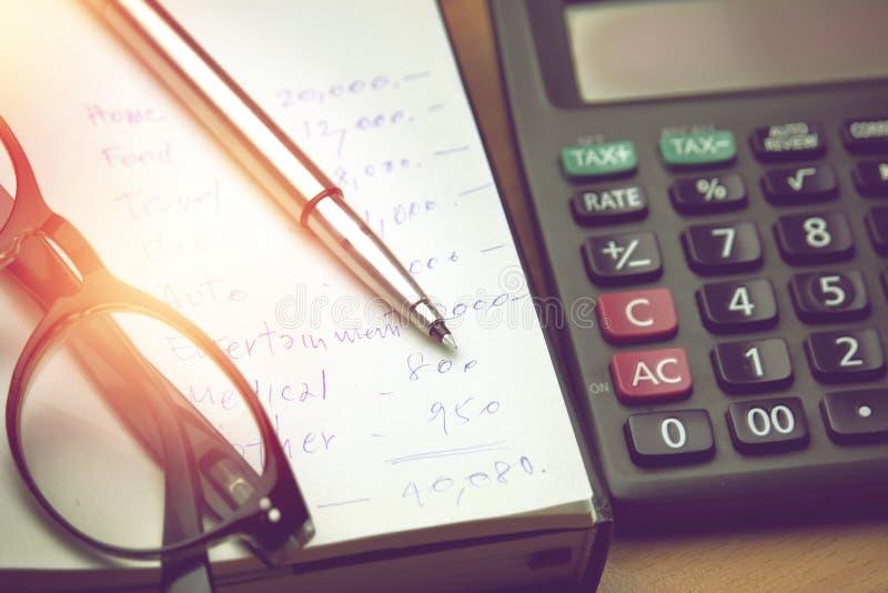 Penna och glasögon på papper för hushållkonto royaltyfri foto