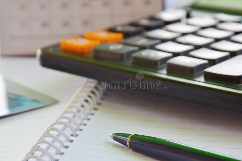 Penna och räknemaskin på boken arkivbild
