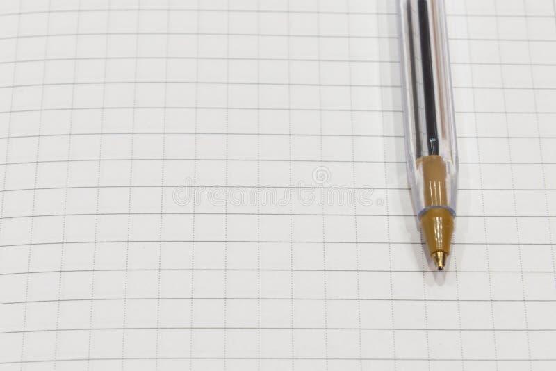 Penna på ett vitt ark av papper i burslutet upp arkivbilder