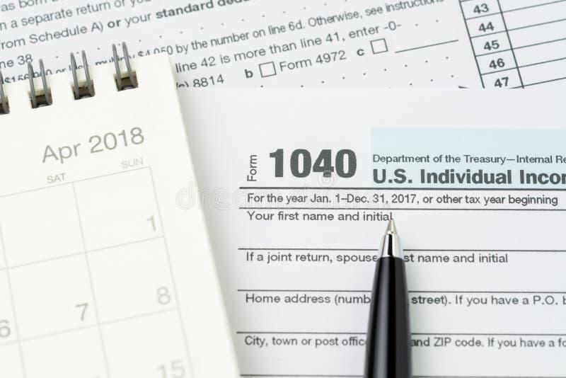 Penna på form för individuell inkomstskatt för 1040 USA fyllande med kalendern, skattundergivenhet eller intäktberäkningsbegrepp arkivfoton