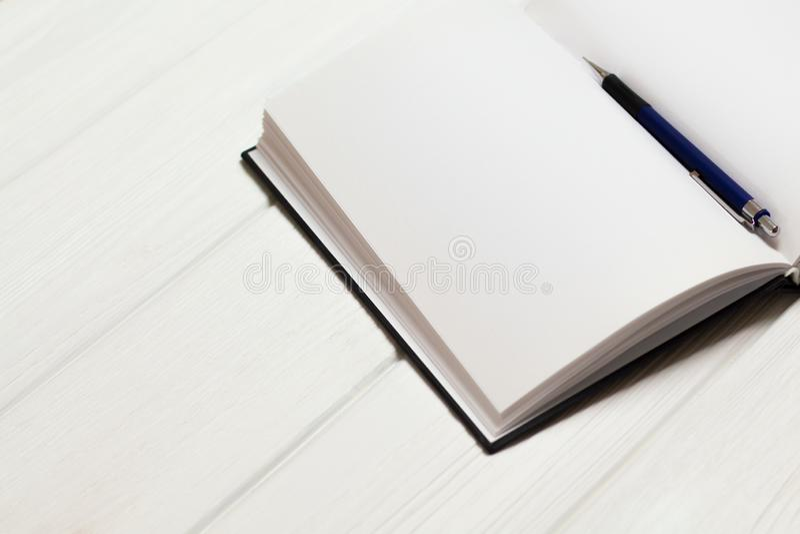 Penna a sfera in taccuino aperto su un fondo di legno bianco Pagine in bianco in taccuino Concetto - scrittura libera pulito fotografie stock libere da diritti