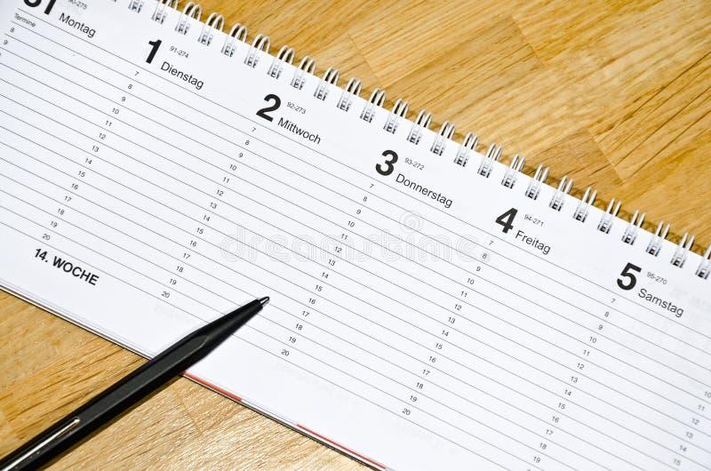 Penna som ligger på schema med dagarna av veckan i tysk royaltyfri bild