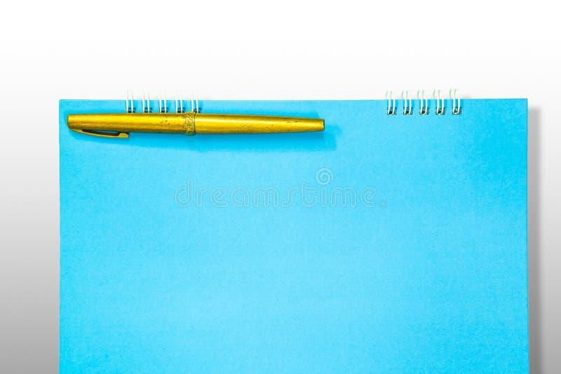Penna stilografica dell'oro e taccuino blu fotografie stock libere da diritti