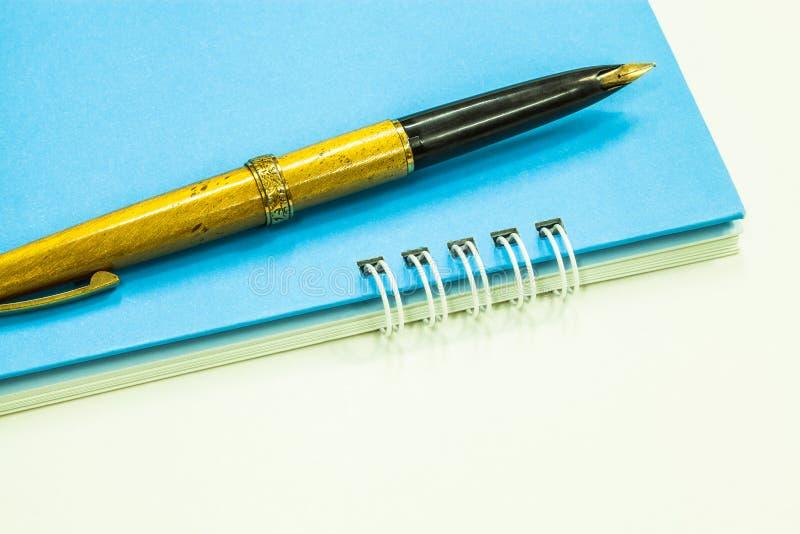 Penna stilografica dell'oro e taccuino blu fotografie stock