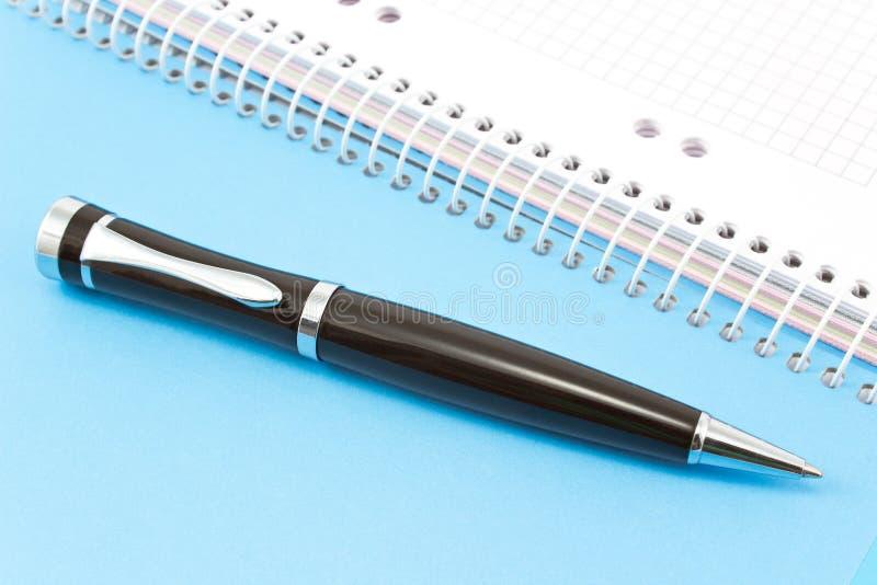 Penna sul blocco note a spirale blu immagine stock