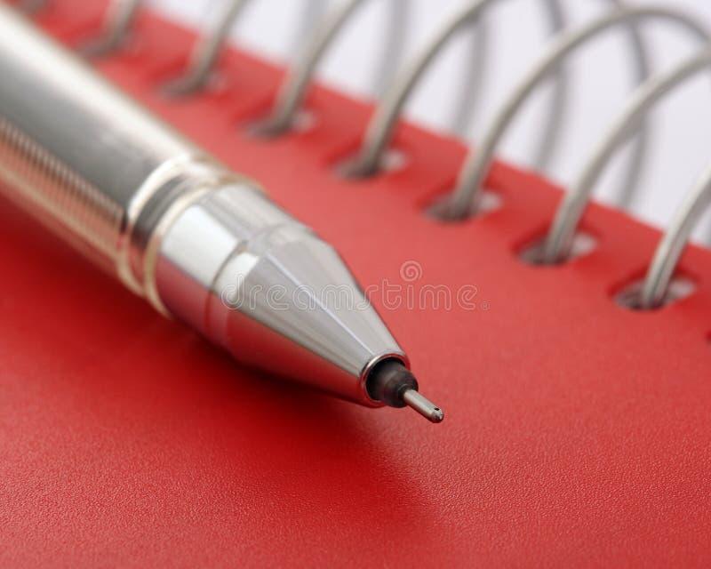 Penna sul taccuino rosso immagine stock libera da diritti