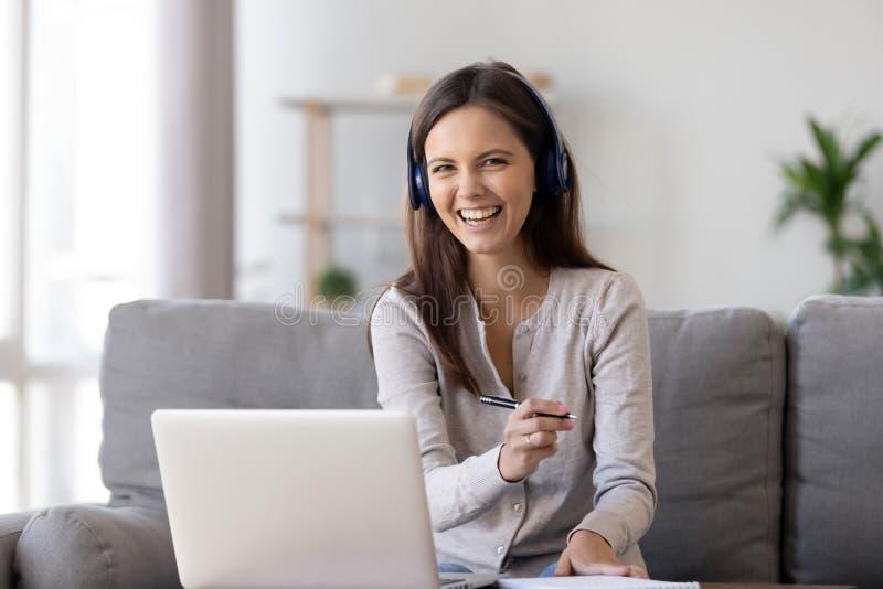 Pennan för hörlurar för kvinnan gör den bärande rymmande anmärkningar som lär bruksbärbara datorn royaltyfri fotografi