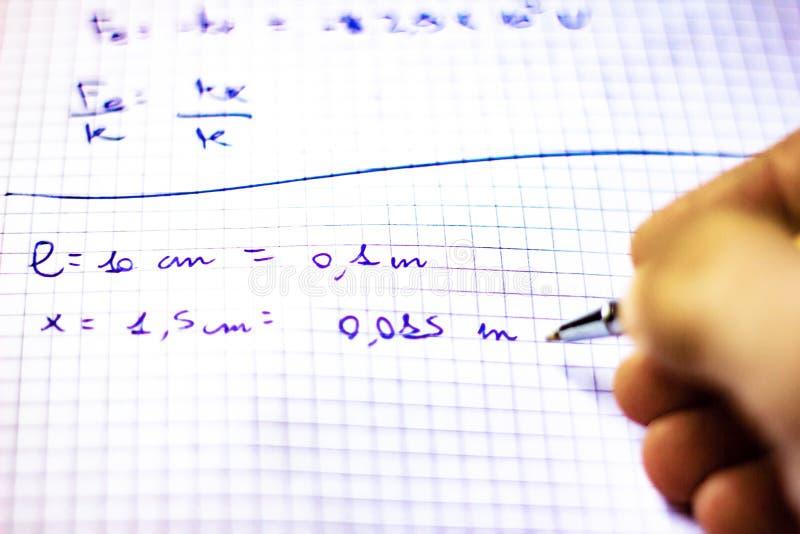Pennan på en anteckningsbok med fyrkanter som är skriftliga med formler, skolastarter i September, nu är det, precis en kort stun arkivbilder