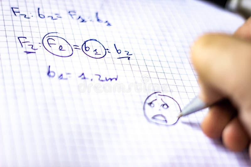 Pennan på en anteckningsbok med fyrkanter som är skriftliga med formler, skolastarter i September, nu är det, precis en kort stun royaltyfri bild