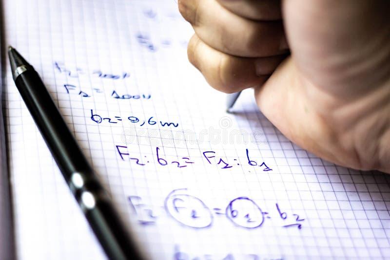 Pennan på en anteckningsbok med fyrkanter som är skriftliga med formler, skolastarter i September, nu är det, precis en kort stun arkivbild