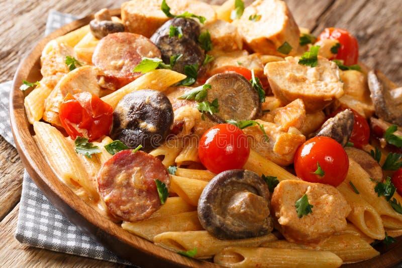 Penne caluroso delicioso de las pastas con el pollo, setas salvajes, salchicha ahumada con el primer cremoso de la salsa de queso imagen de archivo