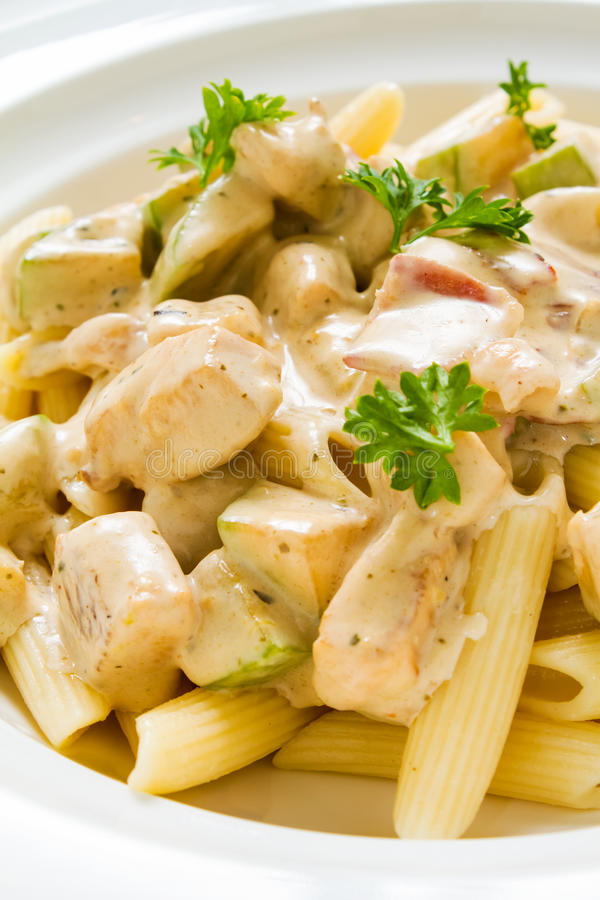 Penne Chicken Alfredo. Close-up studio shot of Penne Chicken Alfredo in rich creamy sauce. Ideal for blogs and recipe books royalty free stock image