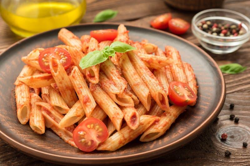 Penne con salsa al pomodoro, basilico ed i pomodori fotografia stock