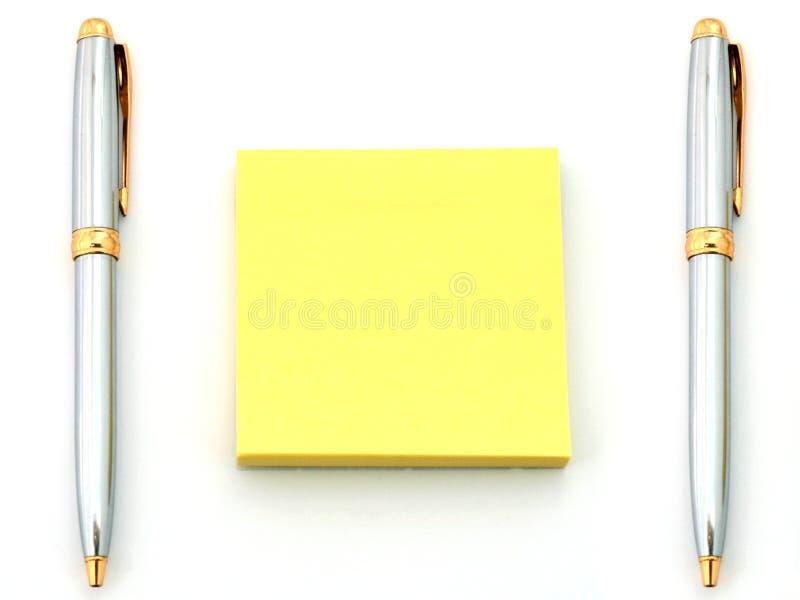 Penne e documento giallo fotografia stock