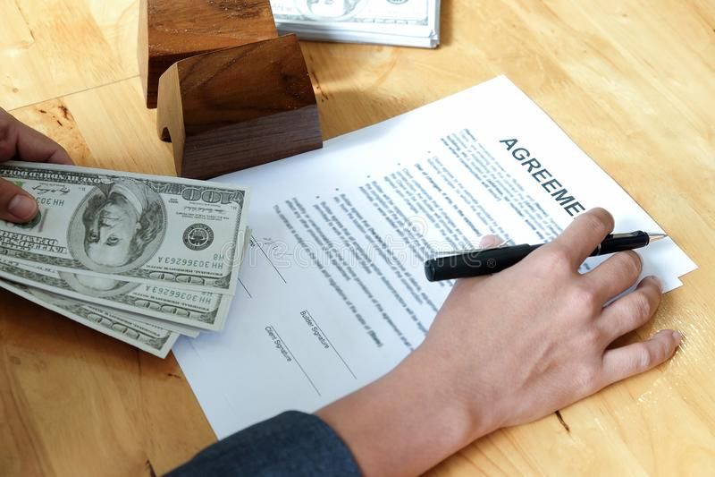 Penne e dollari a disposizione con i documenti ed il modello di accordo hous fotografia stock libera da diritti
