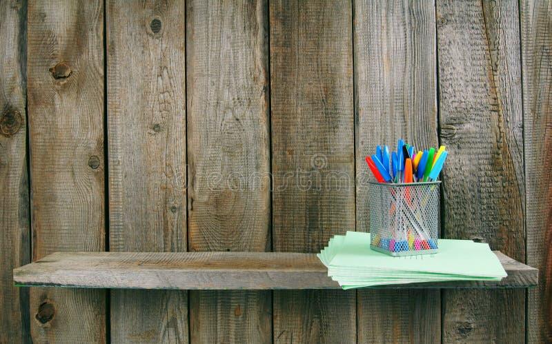 Penne e scrittura-libri su uno scaffale di legno fotografia stock
