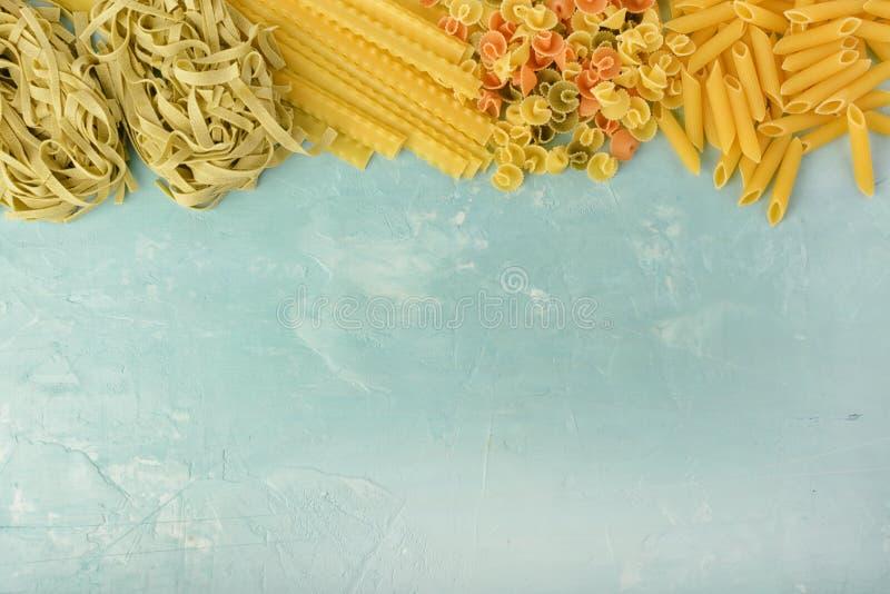 Penne, Mafalde, Tagliatelle, Spaghetti bovenop een blauwe achtergrond wordt opgemaakt die Mooie samenstelling van deegwaren met r royalty-vrije stock fotografie