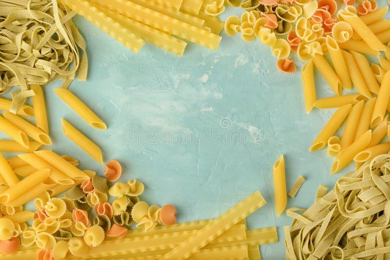 Penne, Mafalde, Tagliatelle, Spaghetti die in een cirkel op een blauwe achtergrond wordt opgemaakt Mooie samenstelling van deegwa stock afbeeldingen