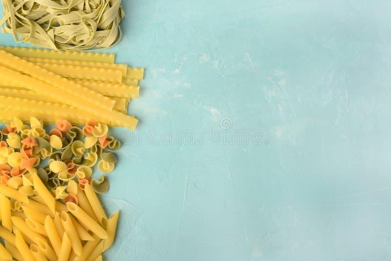 Penne, Mafalde, Tagliatelle, Spaghetti op een blauwe achtergrond wordt opgemaakt die Mooie samenstelling van deegwaren met ruimte stock foto's