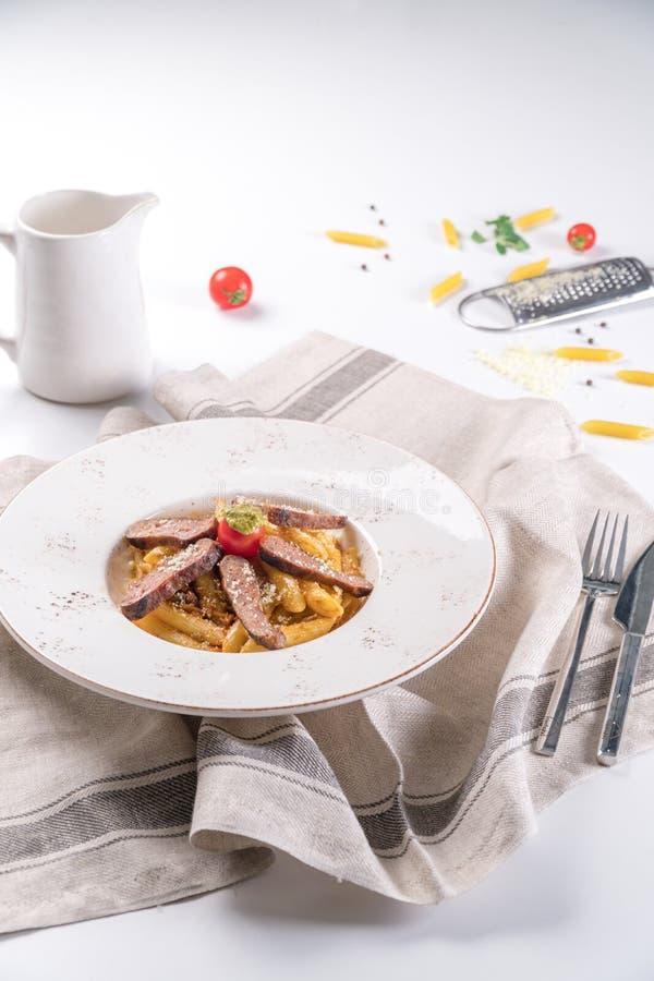 Penne makaron z Piec na grillu stków plasterkami i kumberland na nim pomidoru i Pesto fotografia royalty free