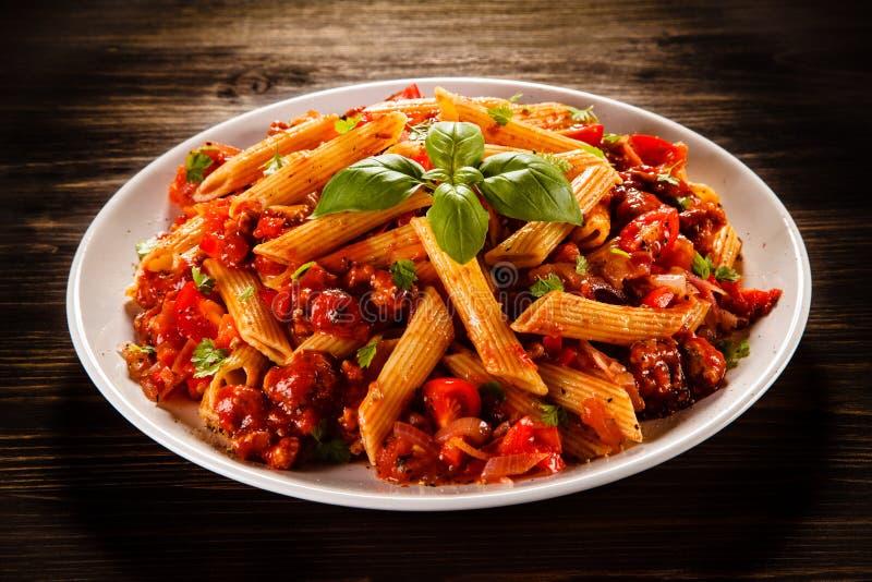 Penne met vlees, tomatensaus en groenten stock afbeelding
