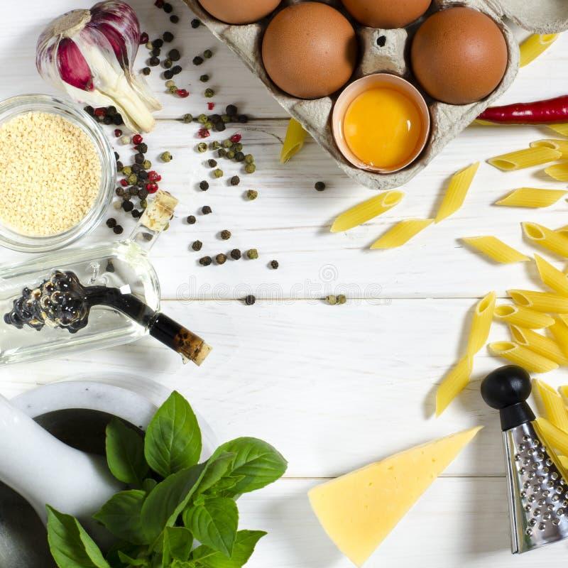Penne Pasta, albahaca verde, parmesano, sésamo, ajo, chile, huevos miente en una tabla blanca del árbol Visi?n desde arriba fotos de archivo