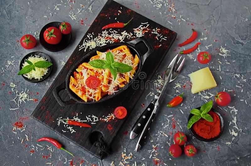Penne pasta with Arrabiata sauce in a cast iron pan on a grey table. Fresh cherry tomatoes, chili peppers and Parmesan cheese stock image