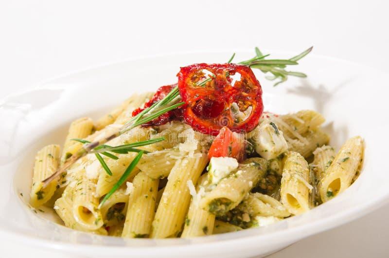 Penne Pasta avec du feta de fromage, des épinards, le pesto et le tomat séché au soleil photos stock