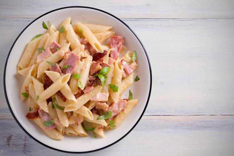 Penne pasta with bacon and sundried tomatoes. Alfredo penne pasta on white plate on wooden table. Overhead, horizontal royalty free stock photo
