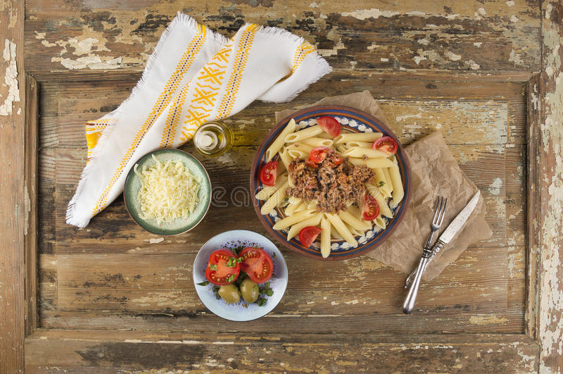 Penne pasta with bolognese sauce, bowls of snacks royalty free stock image