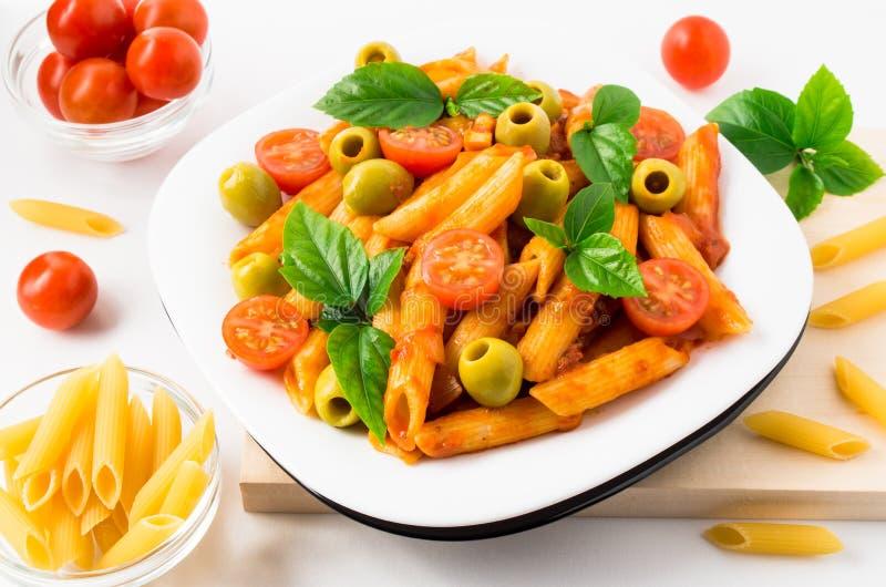 Penne pasta dekorerade med körsbärsröda tomater, oliv och örter arkivbilder