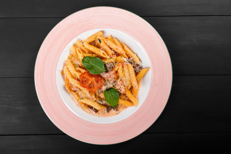 Penne pasta i ostsås med nötköttkött, tomater, parmesan, basilika på plattan på svart träbakgrund fotografering för bildbyråer