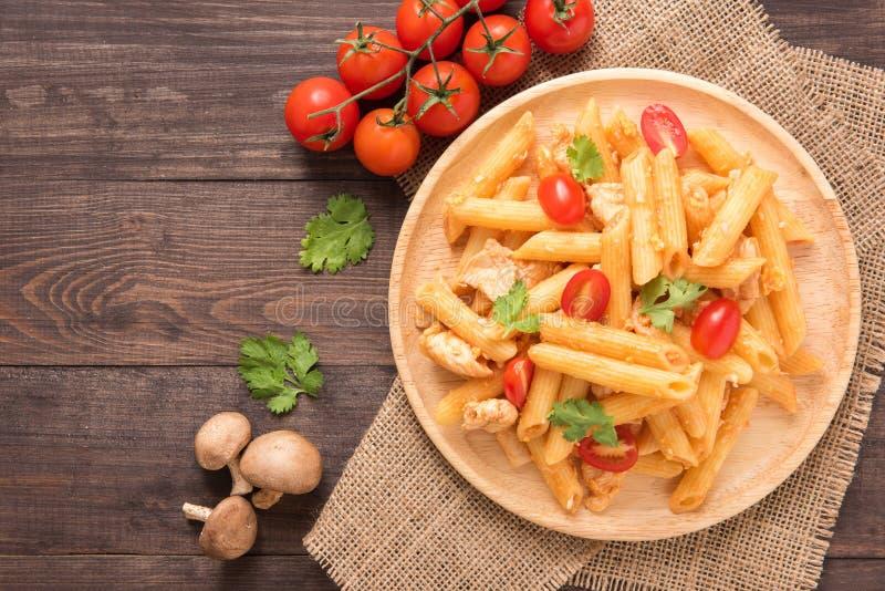 Penne pasta i tomatsås med höna på en träbakgrund royaltyfria bilder