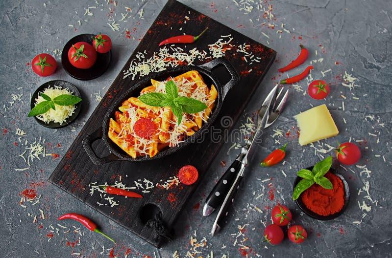 Penne pasta med Arrabiata sås i en gjutjärnpanna på en grå tabell fotografering för bildbyråer