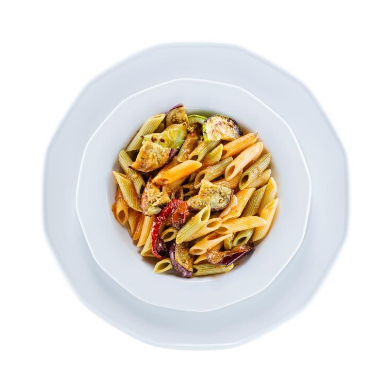 Penne pasta med grillade grönsaker över vit, med banan royaltyfria bilder