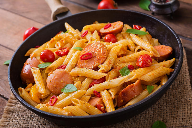 Penne pasta med tomatsås med korven, tomater, grön basilika dekorerade i en stekpanna royaltyfri foto