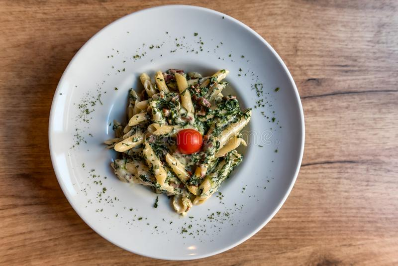 Penne pasta with prosciutto and spinach royalty free stock photography