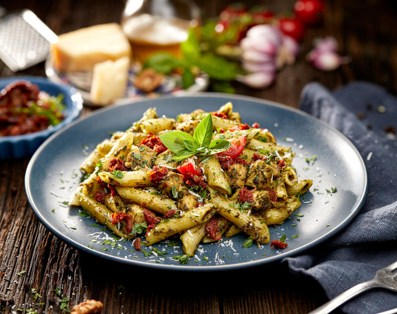 Penne pasta with spinach, sun dried tomatoes and chicken on plate stock images