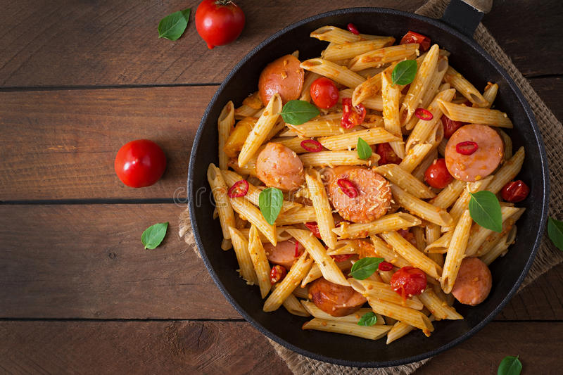 Penne pasta with tomato sauce with sausage, tomatoes, green basil decorated in a frying pan. Penne pasta with tomato sauce with sausage, tomatoes, green basil royalty free stock photo