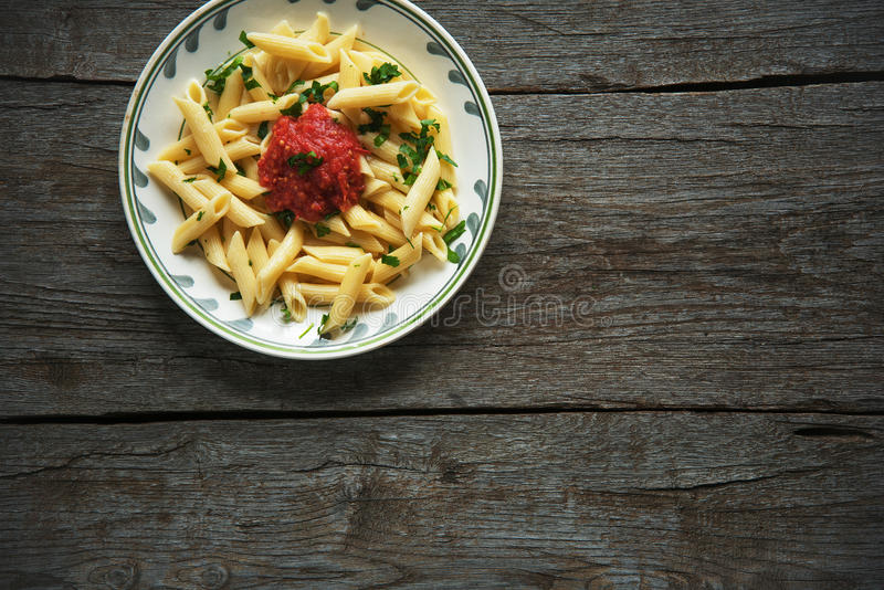 Penne pasta in tomato sauce, tomatoes decorated with parsley on a wooden background stock images