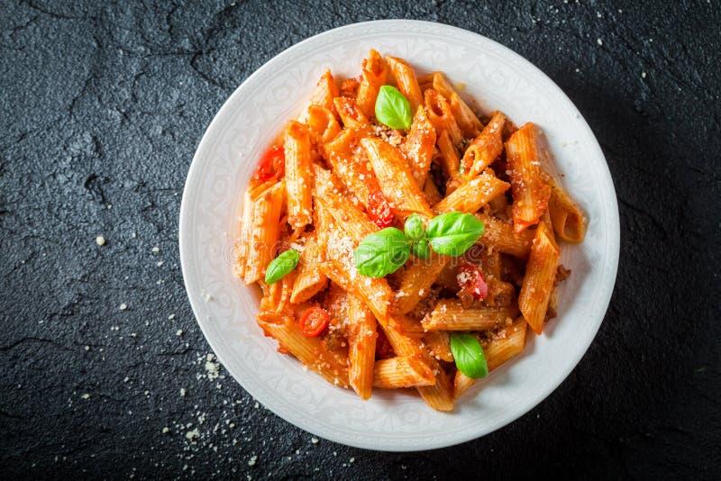 Penne piccante bolognese con parmigiano e basilico fotografia stock